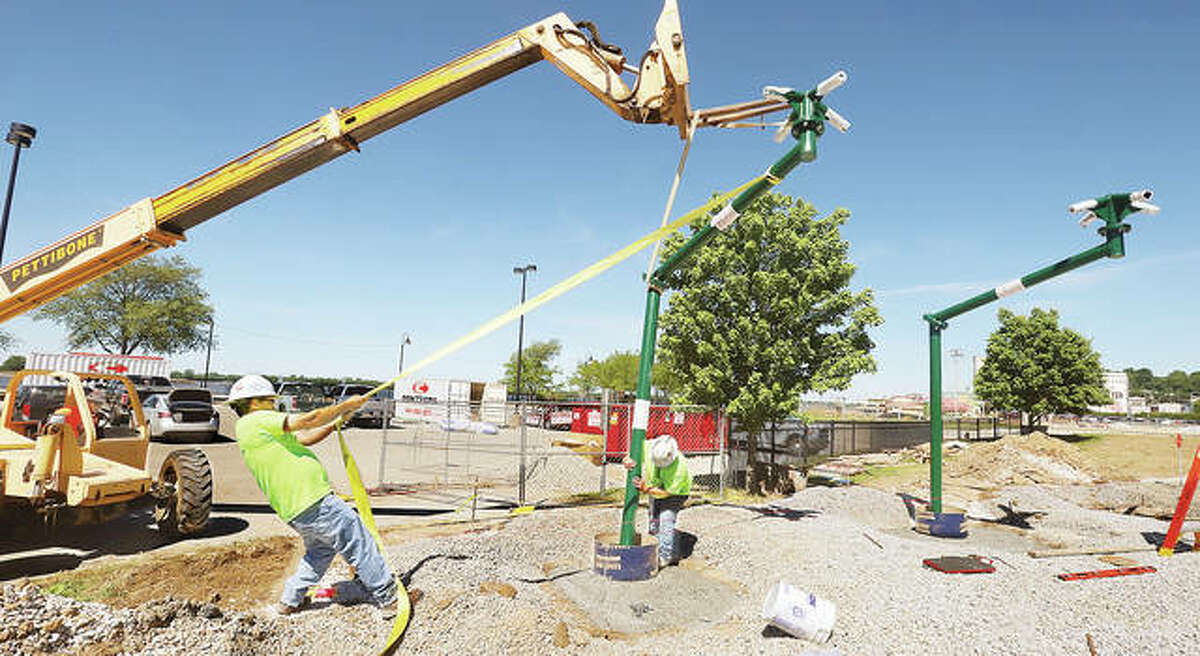 Workers had to put a little muscle into mounting one of the poles that are part of the Alton splash pad's design. The concrete slab has been painted green and blue to represent the Mississippi River bending its way through the area.