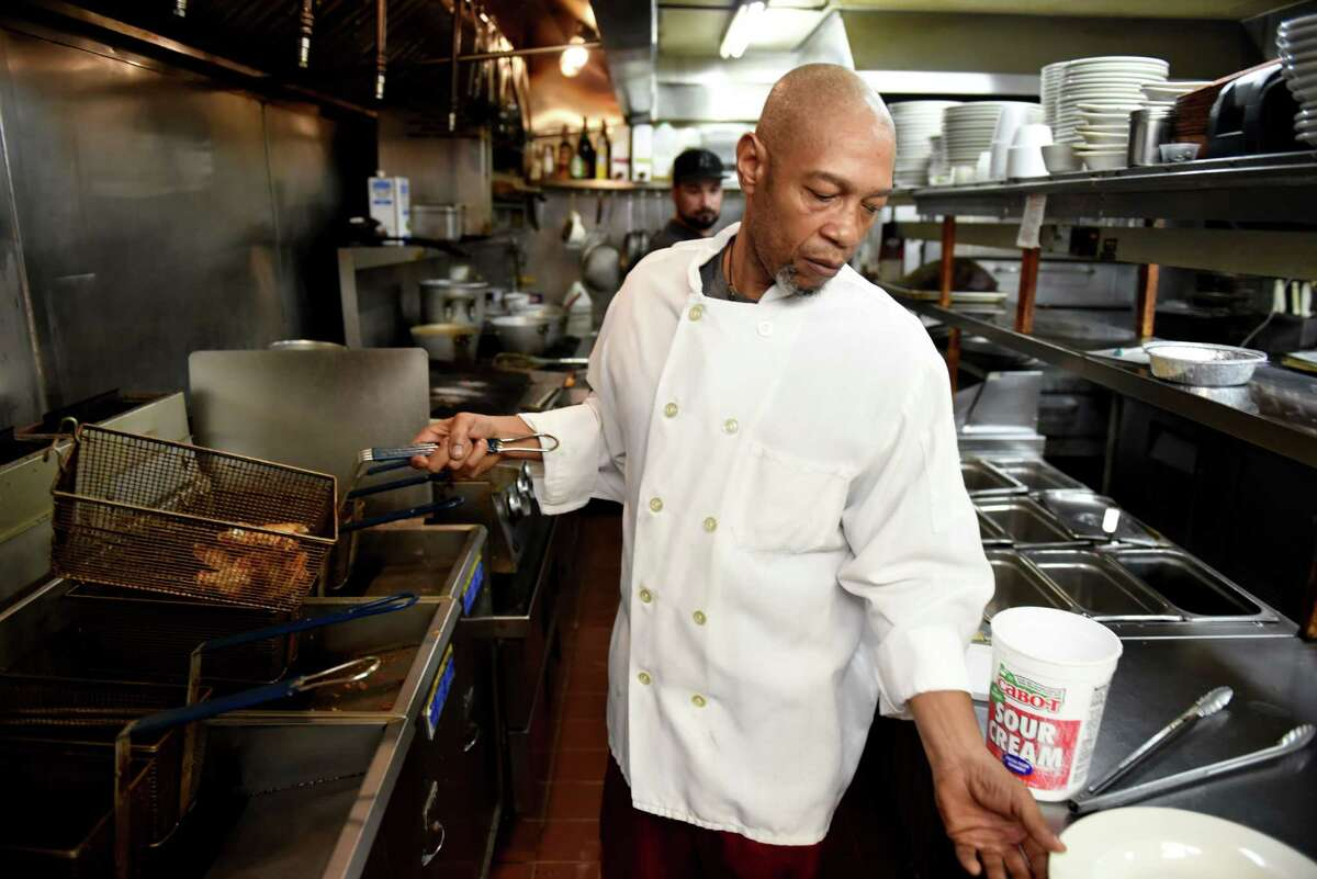Ronnie Daniel, head chef at The Towne Tavern, pulls an order of chicken wings from the deep fryer on Tuesday, June 22, 2021, in Averill Park, N.Y. Prices are rising for the popular finger food. (Will Waldron/Times Union)