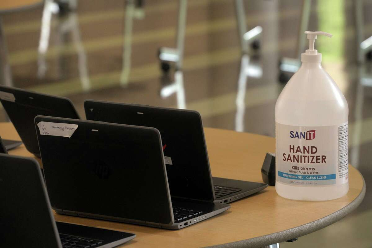 A jug of hand sanitizer sits new to shared laptop computers at stem summer camp at Fairchild Wheeler Interdistrict Magnet High School, in Bridgeport, Conn. Aug. 19, 2020.