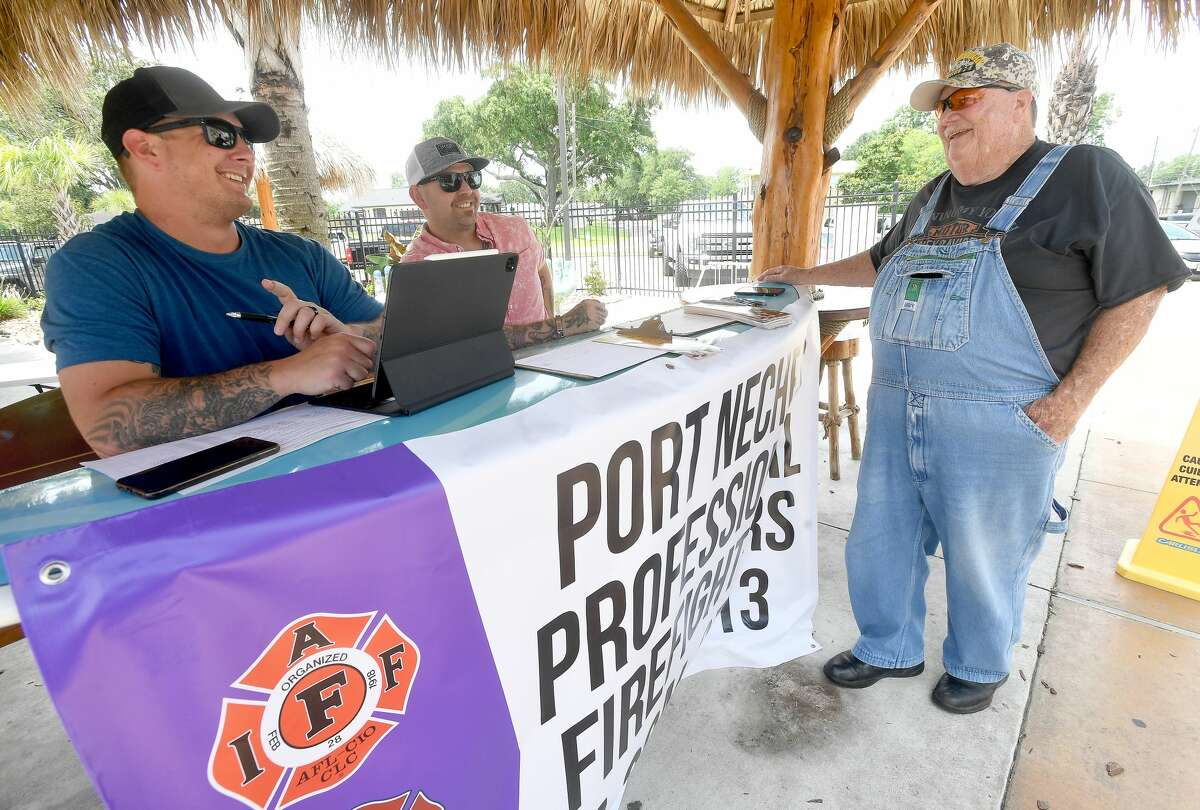 Port Neches Firefighters Tyler Hebert (left) and Jared Jones talk with Jim Rose as they set up at Neches River Wheelhouse to gather resident's signatures to get their union petition on the November ballot. The department, which has been unionized for decades, never had the rights to collective bargaining, which they are hoping Port Neches residents will vote to approve. Photo made Tuesday, June 22, 2021 Kim Brent/The Enterprise