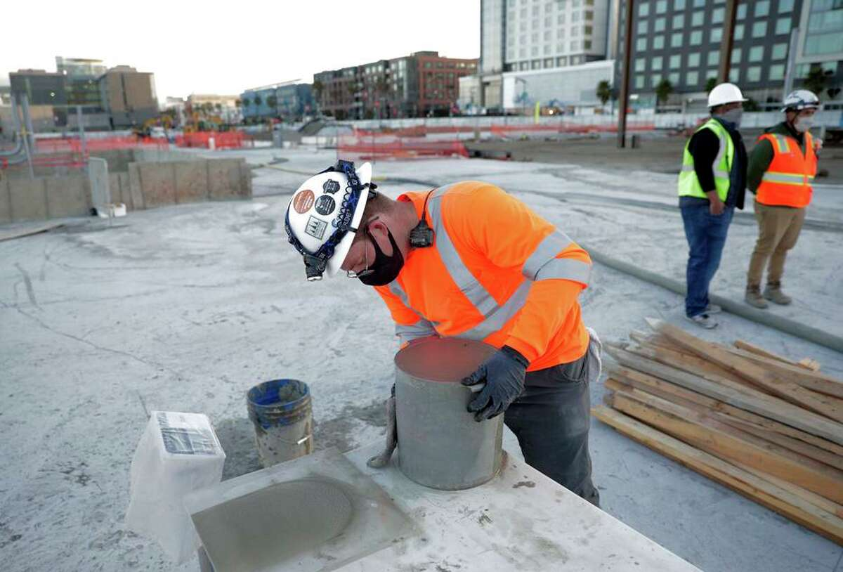 A construction worker with Cell-crete measures the weight of a bucket of lightweight cellular concrete as the company pours in a section of the new Mission Rock development near Oracle Park.