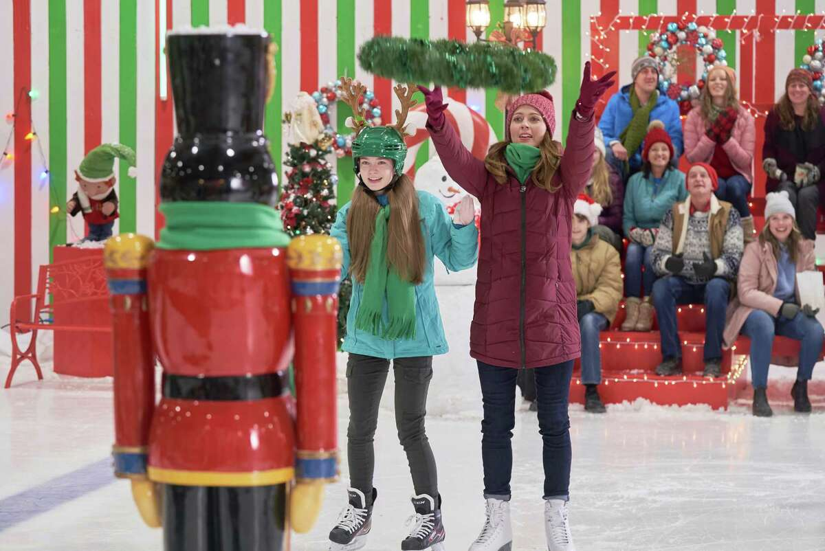 Amy Acker as adorable klutz Maggie greets a giant nutcracker with her daughter Mia (Summer Howell) during some reindeer relays in Hallmark's new Christmas flick.