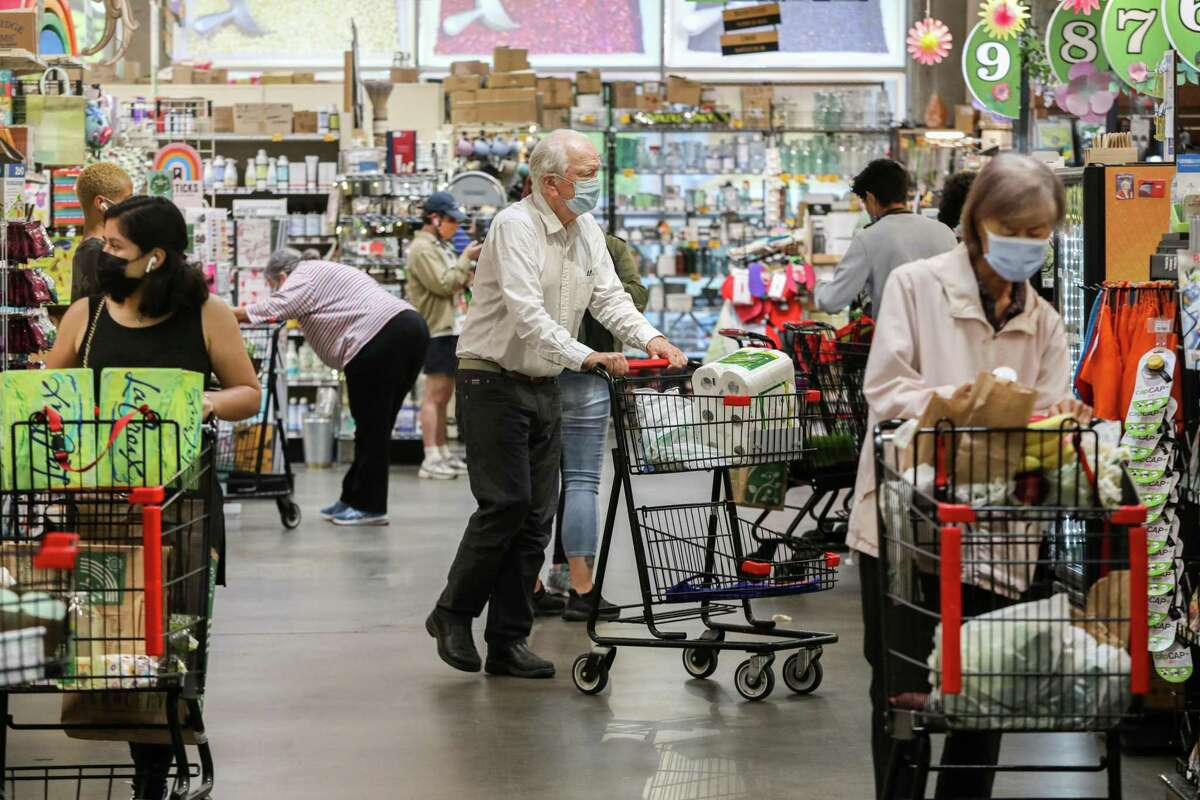 Masked shoppers browse for groceries at Rainbow Grocery in San Francisco. Many stores are letting vaccinated customers shop unmasked, per California guidelines, but it's up to each business.