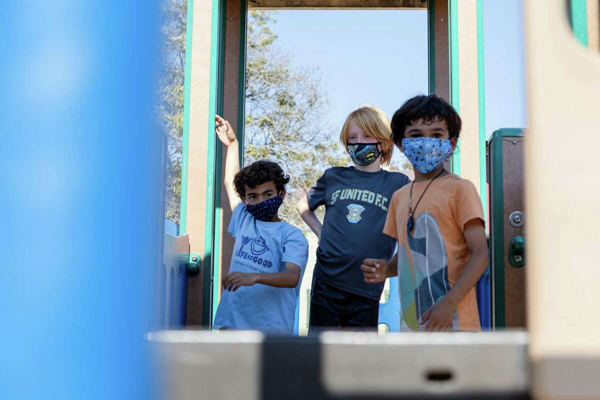 Keshav Mehta, 9, (left) Jasper Barringhaus, 9, and Arin Mehta, 6, wear masks at the Jackson Park playground in San Francisco. Young kids are not yet eligible for vaccination, and the CDC advises masks when in close contact with unvaccinated people.