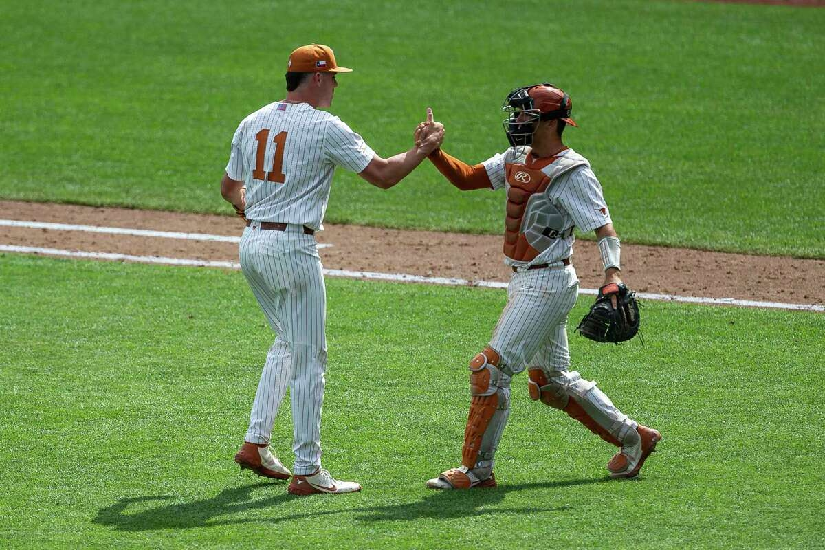 Texas pitcher Tanner Witt (11) and catcher Silas Ardoin (4) shake hands celebrating their win over Tennessee during an NCAA college baseball game in the College World Series Tuesday, June 22, 2021, at TD Ameritrade Park in Omaha, Neb. (AP Photo/John Peterson)