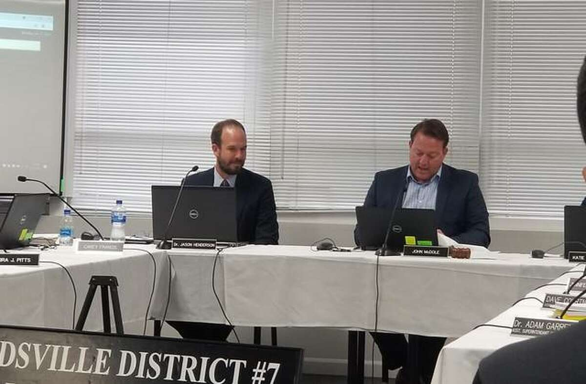 District 7 Board of Education John McDole reads the plaque the board presented to Henderson during the regular board meeting on June 21.