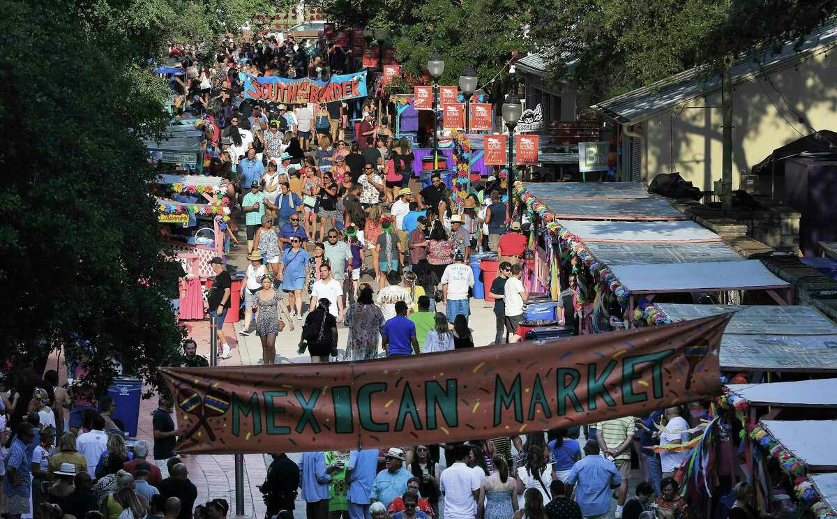 People stroll past food and drink booths during the first night of Night In Old San Antonio on Tuesday, June 22, 2021.
