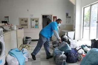 Edward Hambrick organizes customer's laundry as he works at Hambrick Laundry.