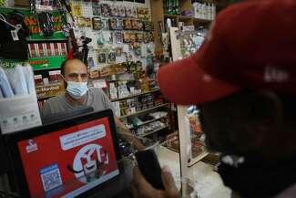 Ali Mohammed, Oak Tree Market owner, waits on a customer.