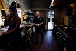 Pedro Rodriguez (right), owner of Santo Coyote, works in the kitchen as he talks with his daughter Yesenia Rodriguez (left).