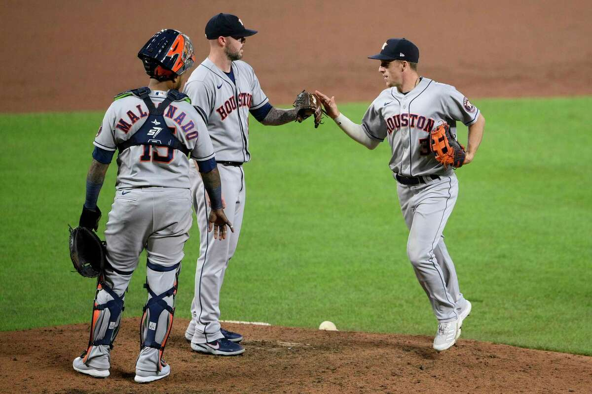 Houston Astros center fielder Myles Straw, right, celebrates with relief pitcher Ryan Pressly, center, and catcher Martin Maldonado (15) after a baseball game against the Baltimore Orioles, Tuesday, June 22, 2021, in Baltimore. The Astros won 3-1. (AP Photo/Nick Wass)