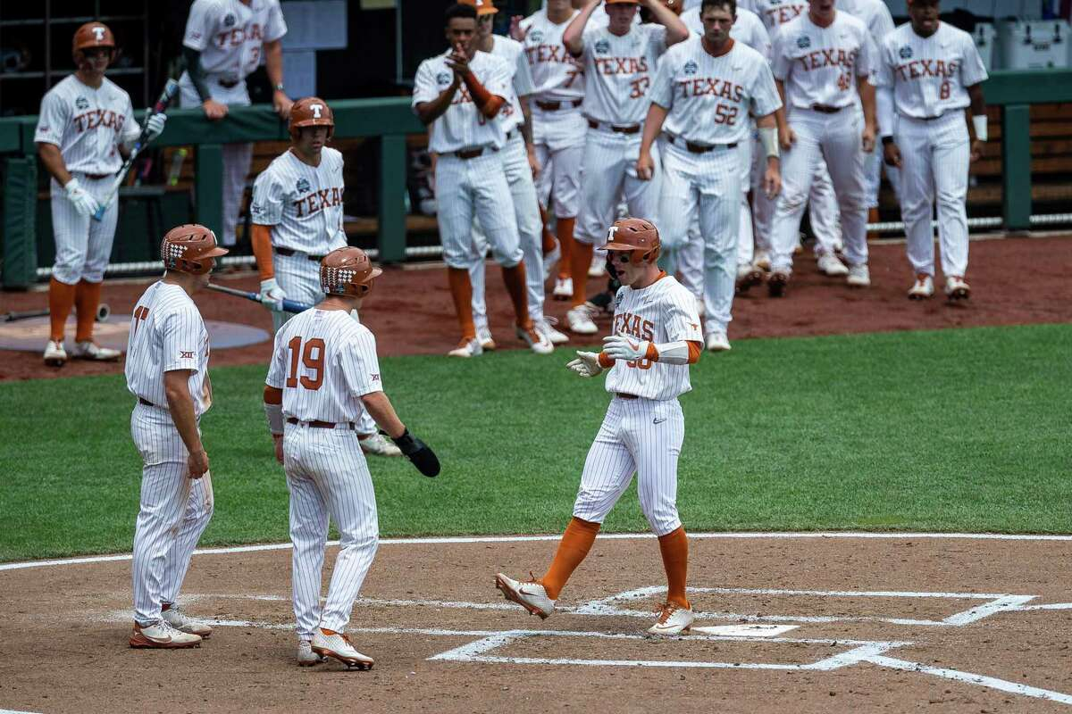 Eric Kennedy, right, crosses home plate after his three-run homer in the second inning Tuesday gave Texas a 3-2 lead.