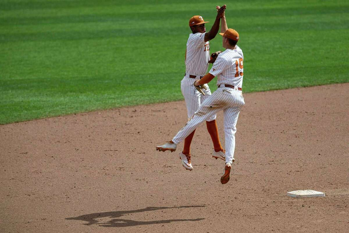 Texas' Trey Faltine, left, and Mitchell Daly high-five to celebrate winning Tuesday's elimination game against Tennessee.