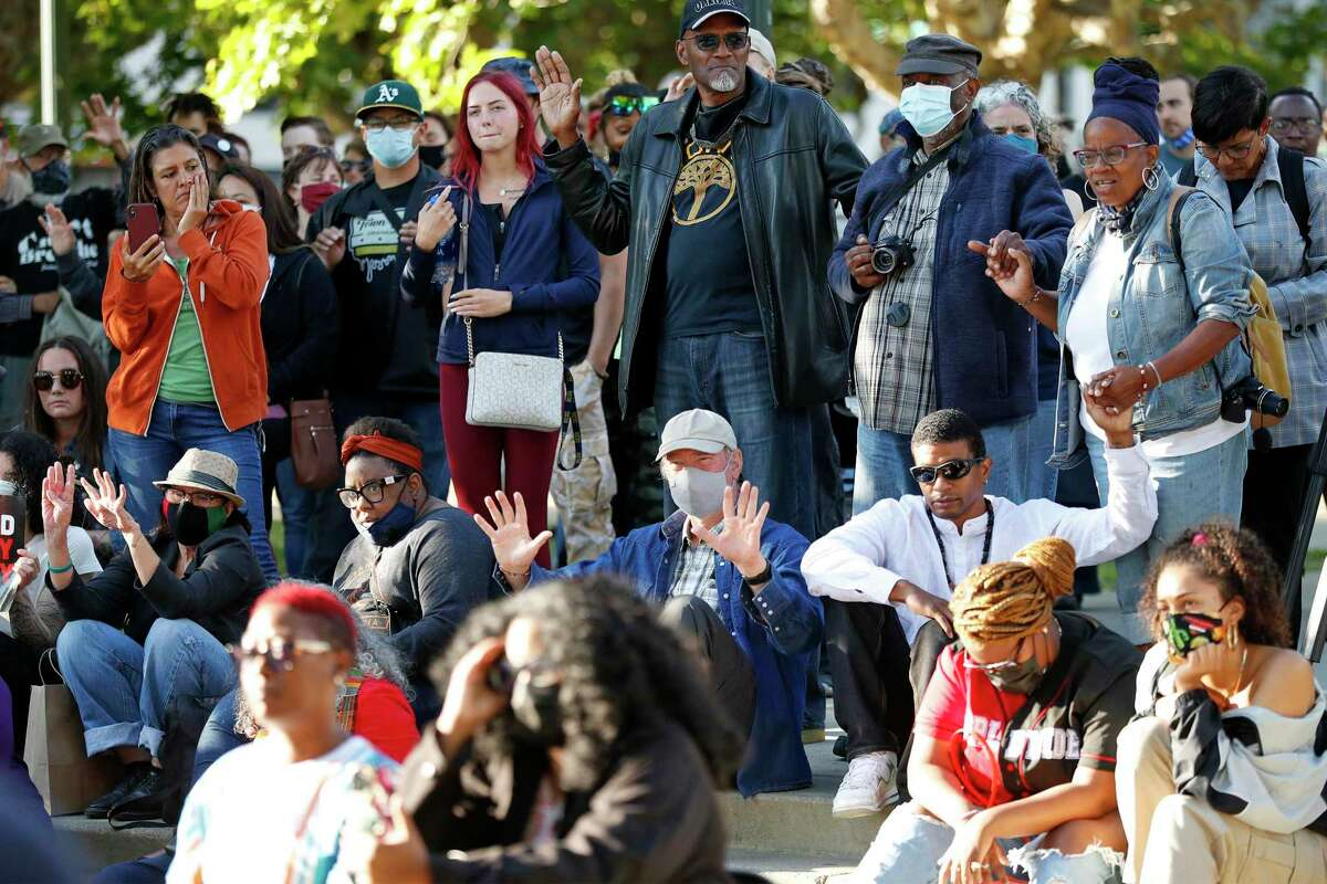 Community members hold hands and raise their hands as Oakland City Councilmembers Nikki Fortunato Bas and Carroll Fife host a vigil to call for peace following Juneteenth shootings at Lake Merritt in Oakland, Calif., on Tuesday, June 22, 2021.
