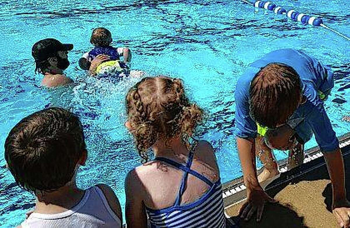 Children watch from the edge of the pool as a participant in Winchester's swim camp gets a lesson. The camp started Monday and continue through July 2 to provide basic overviews of water safety and instructions on swimming to those from birth up. Sessions are divided into four age groups.