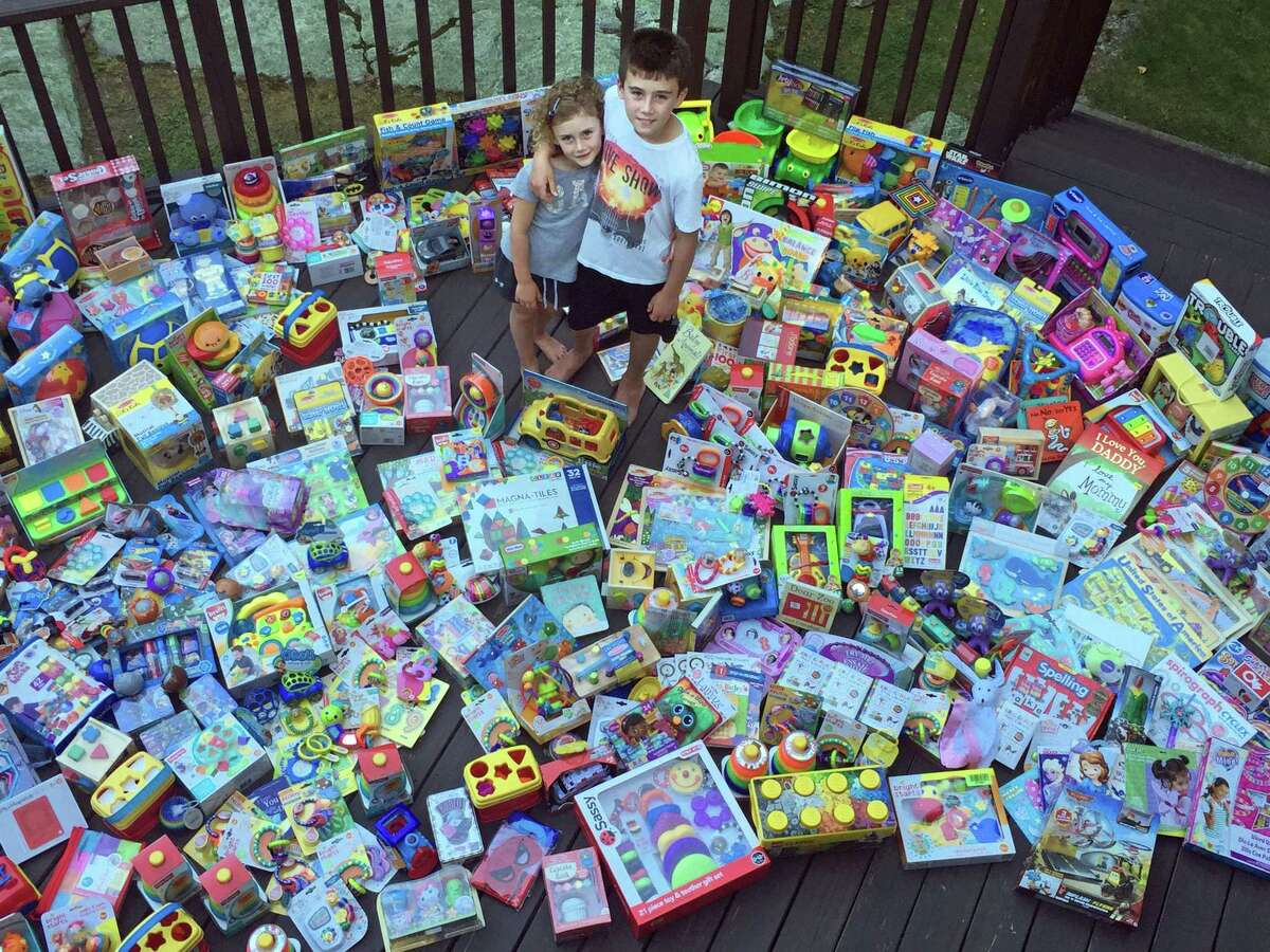 Owen and Emmy Bernheim with some of the 701 toys they collected from 2016 toy drives and birthday parties