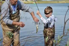 (From left) Scott Heintzelman helps Emmet Heintzelman with a rock bass during the Kids Fish Day event at Man Made Lake on Wednesday.