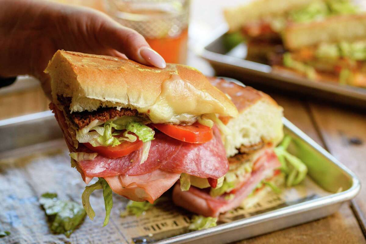 The Sanguiche is crispy eggplant, mortadella, salami, ham, provolone, roasted reds, lettuce, tomato, Italian dressing and fig jam, served hot on a 10-inch grinder roll.
