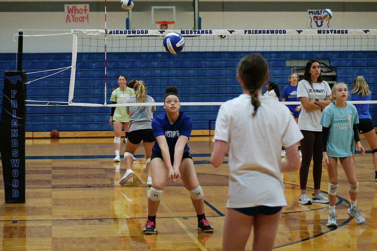 Isabella Punchard and Preslee Alaniz participate in a passing drill during the Friendswood Mustang athletic camp at Friendswood High School.