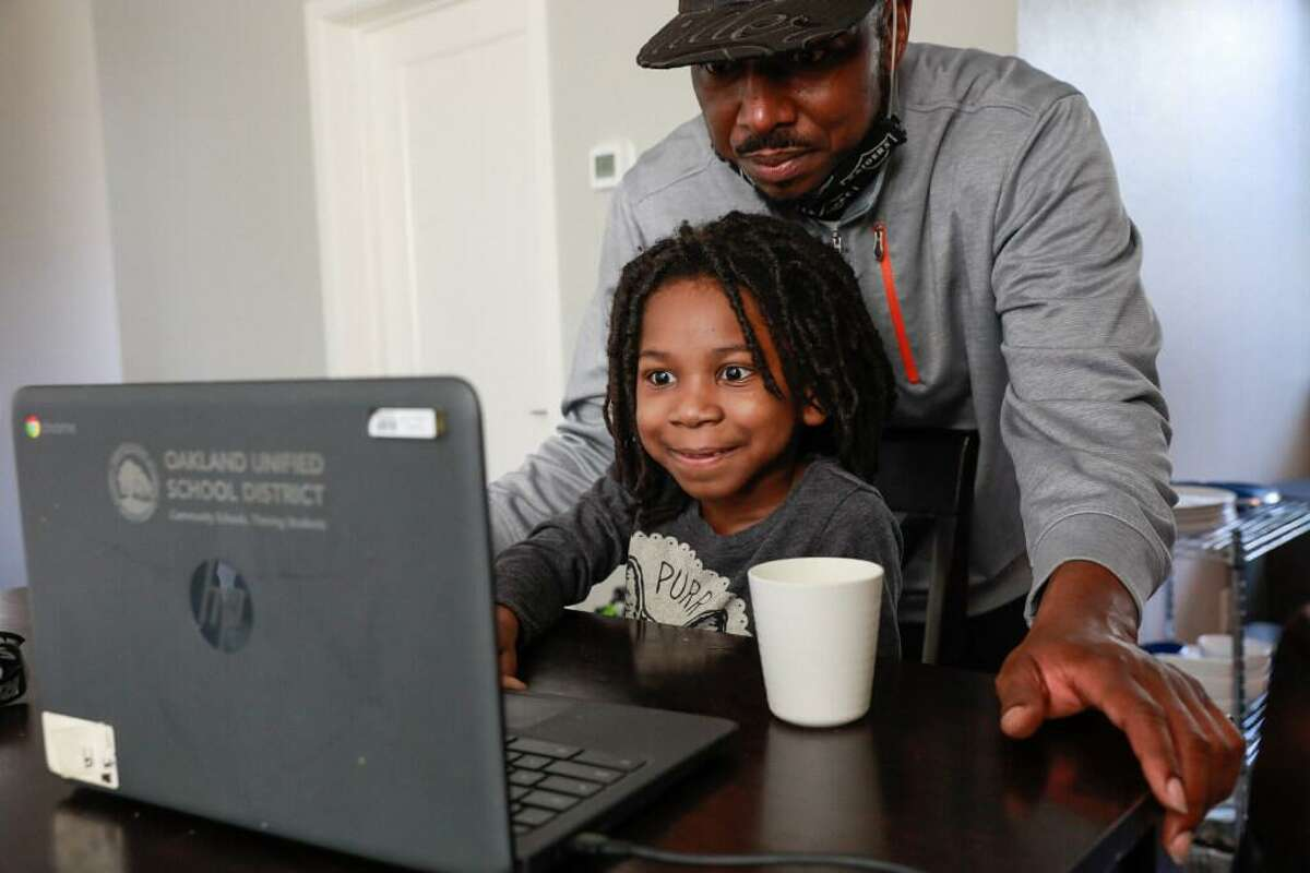 John Jones helps son Josiah, 6, with his virtual learning class at their home in Oakland, California on Friday, Jan. 29, 2021.