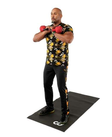 For the double kettlebell squat and rotational press, begin by standing with your feet a little more than shoulder-width apart, with your toes pointing out, holding the kettlebells. Photo: Melissa Phillip, Houston Chronicle / Staff Photographer / © 2021 Houston Chronicle