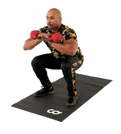 Lower your hips into a squat, keeping your torso erect. Press through your heels at the bottom of the squat., and return to the top position. Photo: Melissa Phillip, Houston Chronicle / Staff Photographer / © 2021 Houston Chronicle