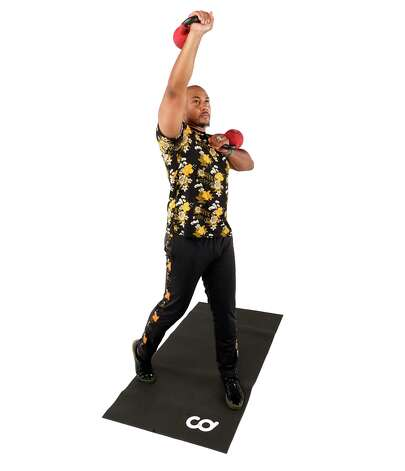 Rotate your torso 90 degrees while pressing the kettlebell overhead. Pivot the ball of your trail foot and return to rack position. Photo: Melissa Phillip, Houston Chronicle / Staff Photographer / © 2021 Houston Chronicle