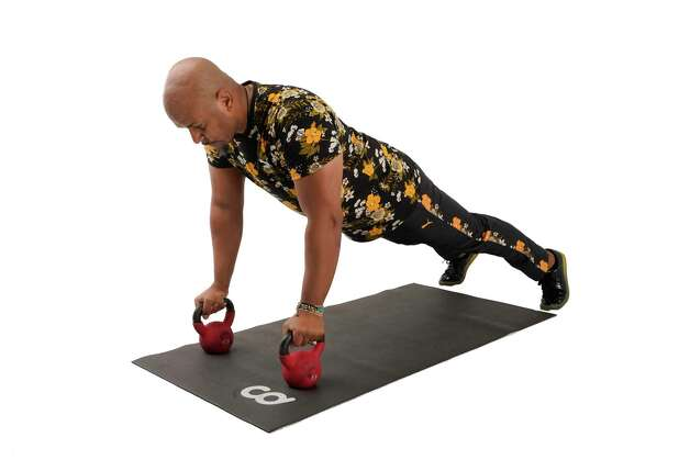 For the renegade row to mountain climbers exercise, grasp kettlebells in a wide plank pushup position with legs slightly apart. Photo: Melissa Phillip, Houston Chronicle / Staff Photographer / © 2021 Houston Chronicle