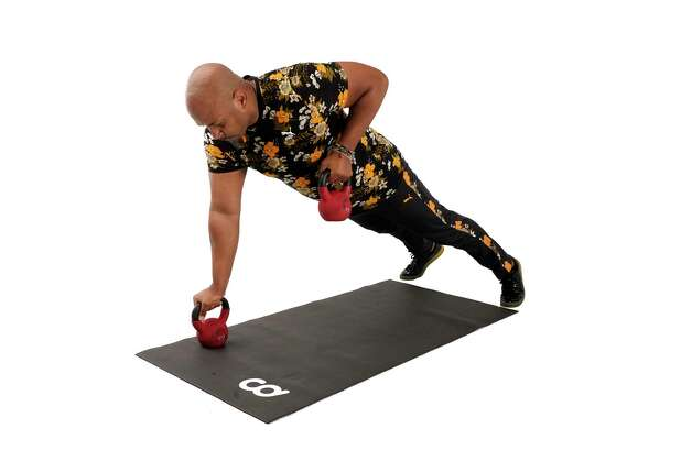 Raise one kettlebell and squeeze your elbow up toward your ribs. Return the kettlebell to floor and repeat on the other side. Photo: Melissa Phillip, Houston Chronicle / Staff Photographer / © 2021 Houston Chronicle