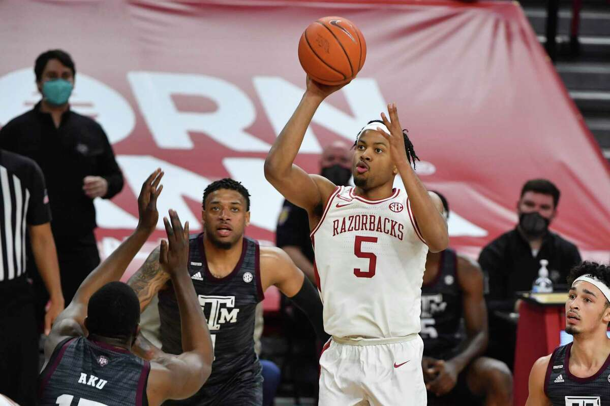 Arkansas guard Moses Moody (5) shoots over Texas A&M defenders during the first half of an NCAA college basketball game in Fayetteville, Ark., Saturday, March 6, 2021. (AP Photo/Michael Woods)