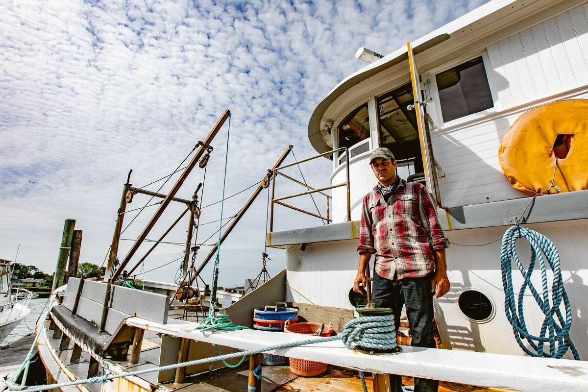 James Bloom stands on one an oyster boat at Copps Island Oysters in Norwalk, Conn., on June 2, 2021.