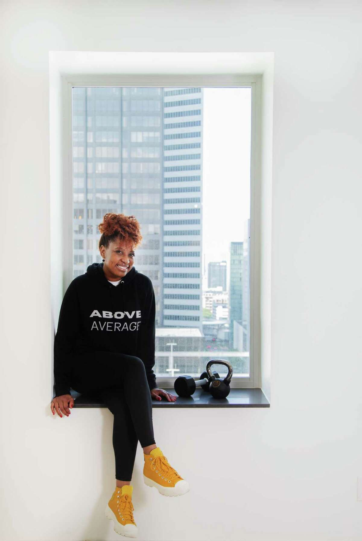 """Dawn Callahan models one of the athletic sportswear hoodies she created with the message """"Above Average,"""" Monday, May 10, 2021, in Houston. Callahan created the clothing during the pandemic as her side project."""
