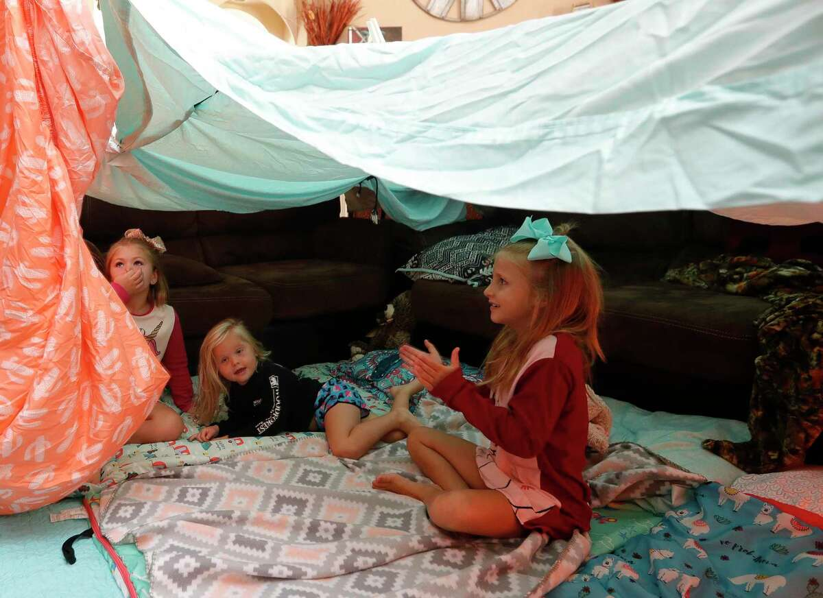 """Adalynn Smart, right, claps as she sits under the family's blanket fort with her sisters, Paisley and Charlee, in their living room as part of Family Promise of Montgomery County's """"Night Without A Bed"""" initiative, Saturday, June 20, 2020, in Montgomery. The nation-wide event is to raise awareness of children and family battling homelessness."""