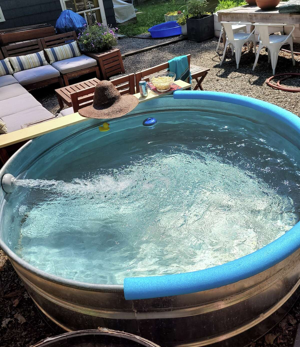 A stock tank pool can help beat the heat for a tiny fraction of the cost of an in-ground pool. DIY it by inserting a filter and pump to keep water clean and safe.