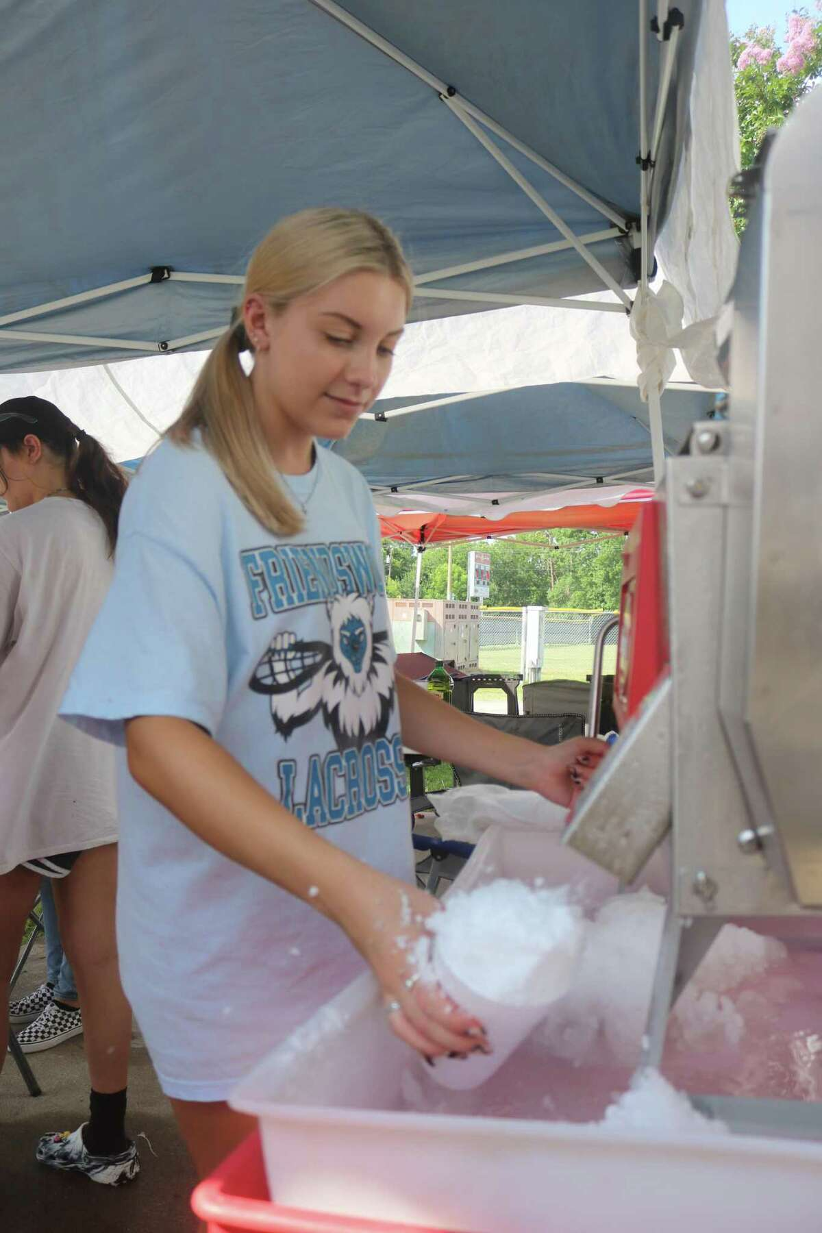 Gracie Varley fills a cup of crushed ice for a customer during her work as a snow-cone-stand operator. As hot as it was on a recent Saturday, Gracie and her co-workers didn't mind getting ice on their hands.