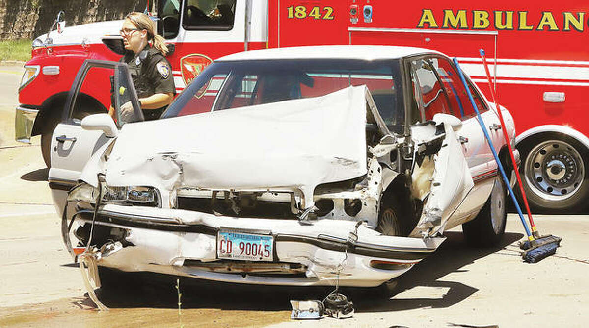 An Alton Police officer stands near a Buick LeSabre after a collision between it and a Chrysler Sebring Wednesday afternoon in Alton. Three people were injured in the accident and taken to area hospitals.