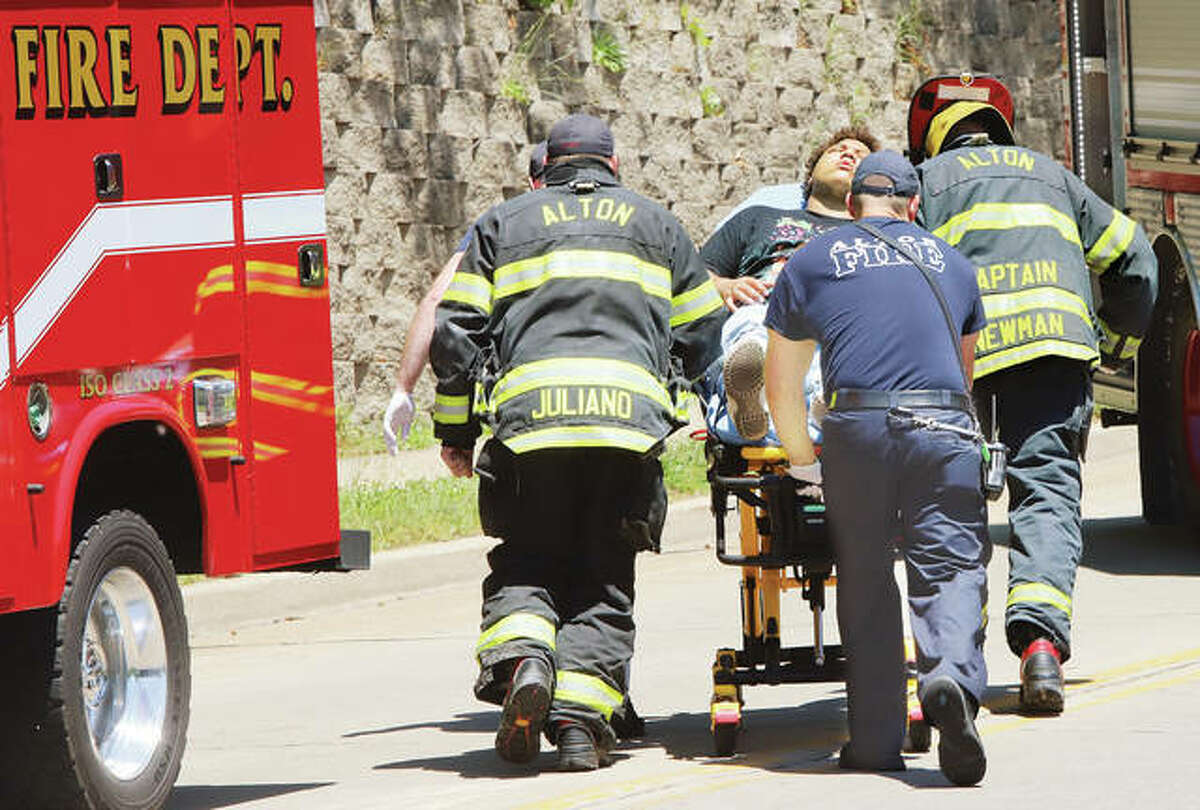 Alton firefighters push a victim from a two-car crash to a waiting ambulance on 20th Street in Alton on Wednesday. All three people involved in the accident were transported to local hospitals with non-life threatening injuries.