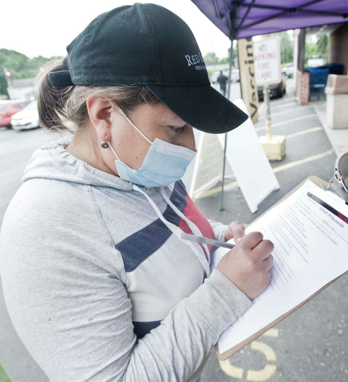 Mirian Aucay, of Danbury, fills out a form prior to receiving a COVID-19 vaccine at CTown Supermarket in Danbury. Tuesday, June 22, 2021