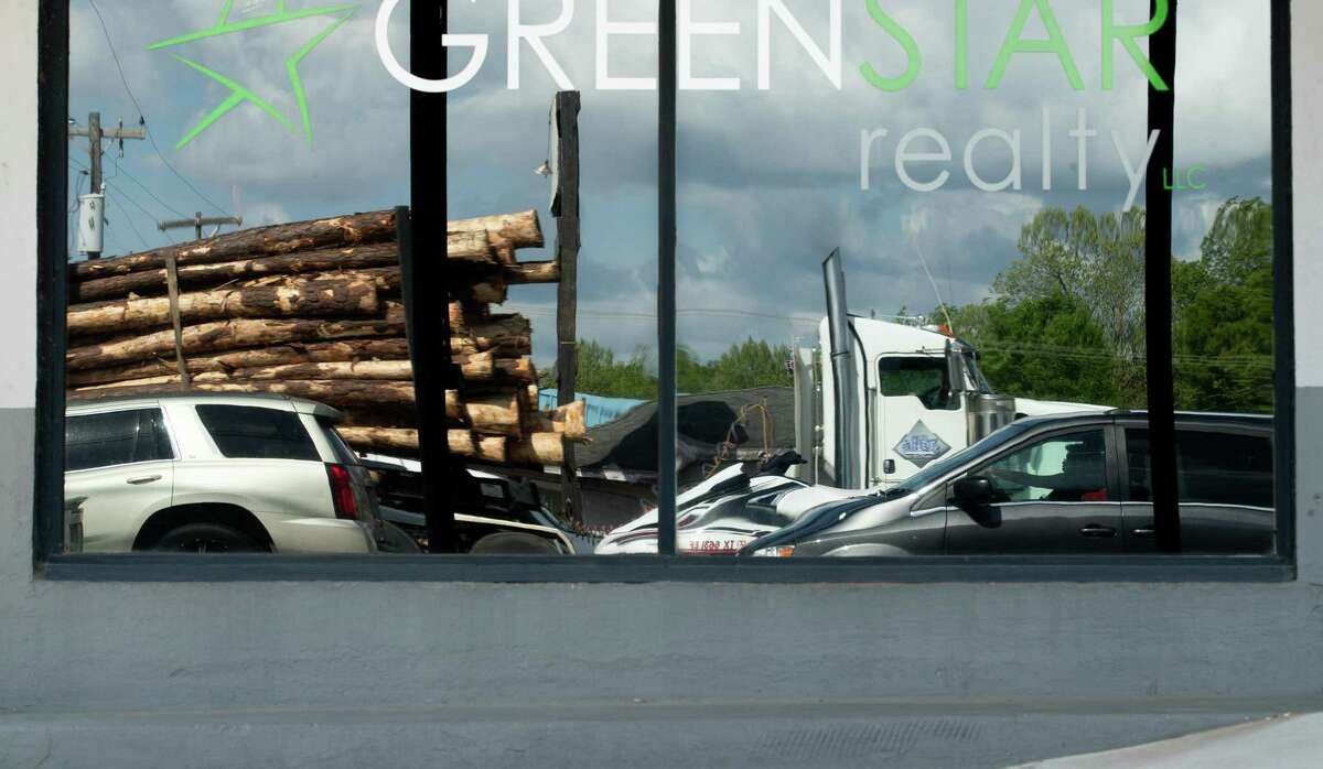 An 18-wheeler transporting tree logs can be seen reflected on a business display on South Wheeler Street, on Tuesday, April 6, 2021, in Jasper, Texas.