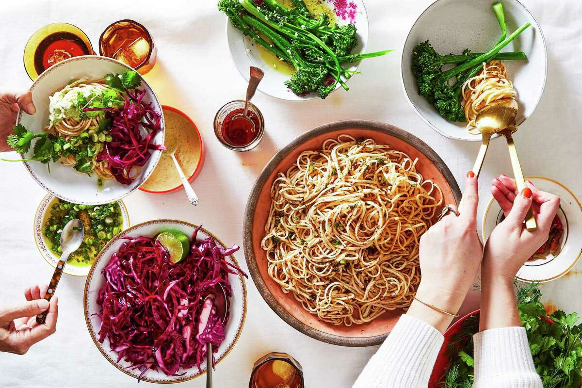 Cold chile noodles, served with fresh herbs, citrusy cabbage, and vegetables. Such assemble-it-yourself meals can help one get more out of cooking for friends by flipping the ratio of time spent working to time spent eating. (Julia Gartland/The New York Times; styled by Kristine Trevino)