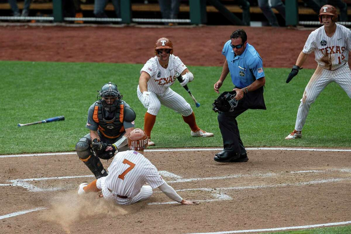 Texas outfielder Douglas Hodo (7) slides into home against Tennessee catcher Connor Pavolony (17) to score in the fourth inning of Tuesday's College World Series elimination game.