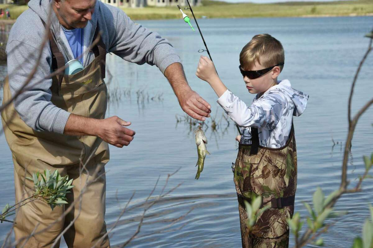 (From left) Scott Heintzelman helps Emmet Heintzelman with a rock bass during the Kids Fish Day event at Man Made Lake on Wednesday. (Arielle Breen/News Advocate)