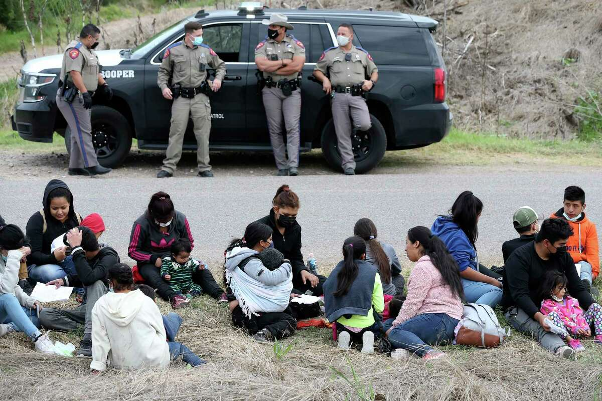 Texas Department of Public Safety troopers wait on U.S. Border Patrol agents after helping in the detention of a group of around 40 migrants April 2 just west of La Joya.