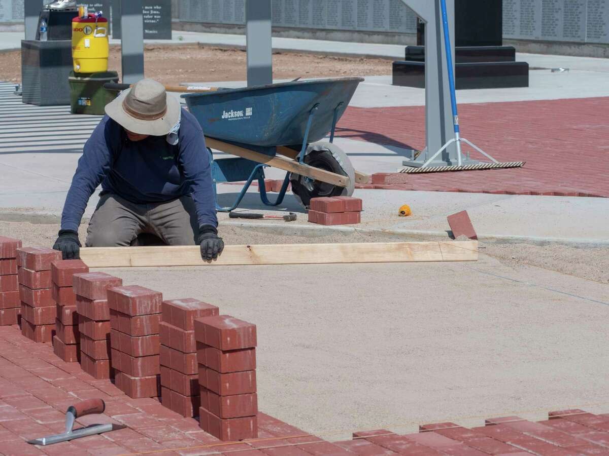 Work continues 06/23/2021 on the Veteran's Memorial in front of the Midland County Annex as Jesus Montoya smooths the sand base for brick work as he and others with Lawn and Tree Tech, LLC work on the pathways in front of the memorial. Tim Fischer/Reporter-Telegram