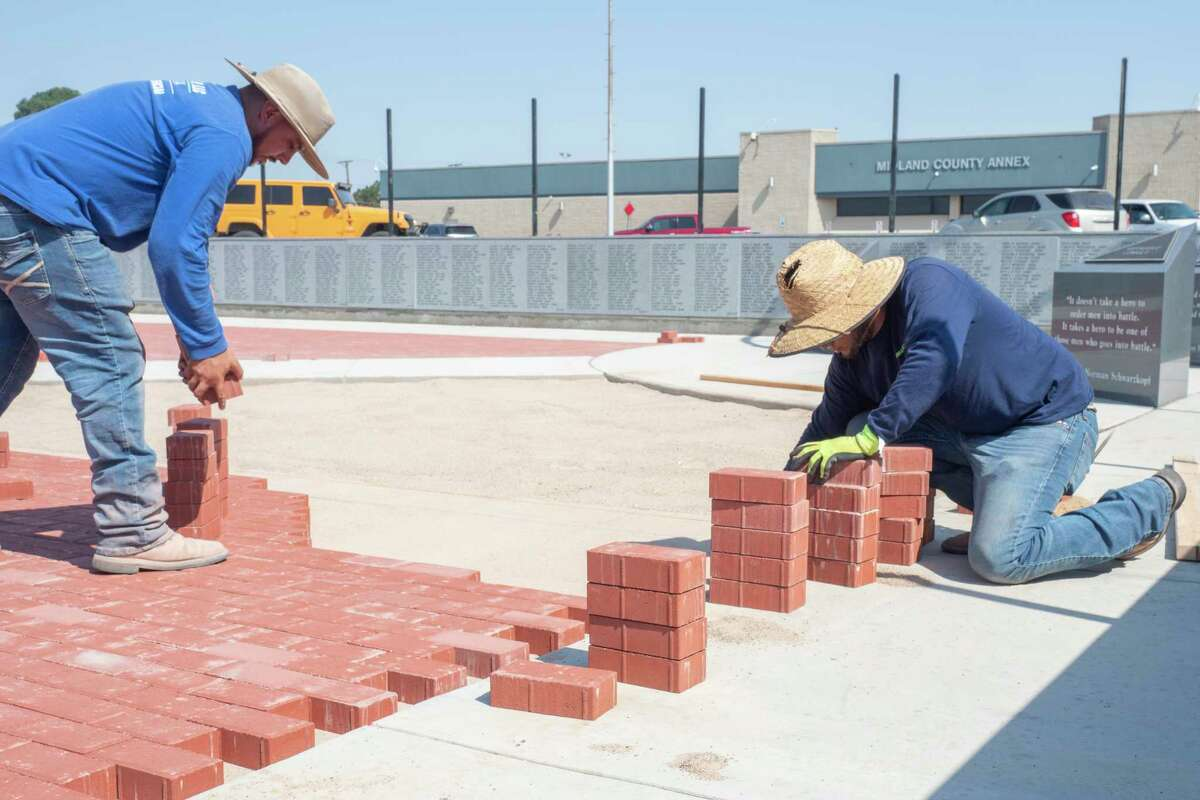 Work continues 06/23/2021 on the Veteran's Memorial in front of the Midland County Annex as Diego Lozano places bricks as Gabriel Garcia brings stacks of bricks as they and others with Lawn and Tree Tech, LLC work on the pathways in front of the memorial. Tim Fischer/Reporter-Telegram