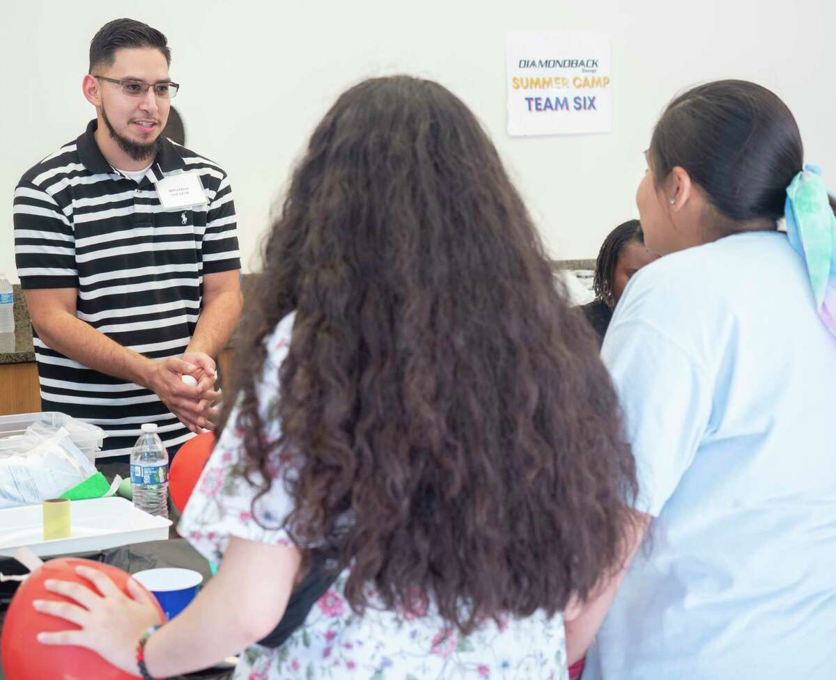 Diamondback Energy employee Jonathan Salazar works with seventh and eighth graders from Opportunity Tribe 06/23/2021 during STEM Camp at Diamondback Energy. Tim Fischer/Reporter-Telegram