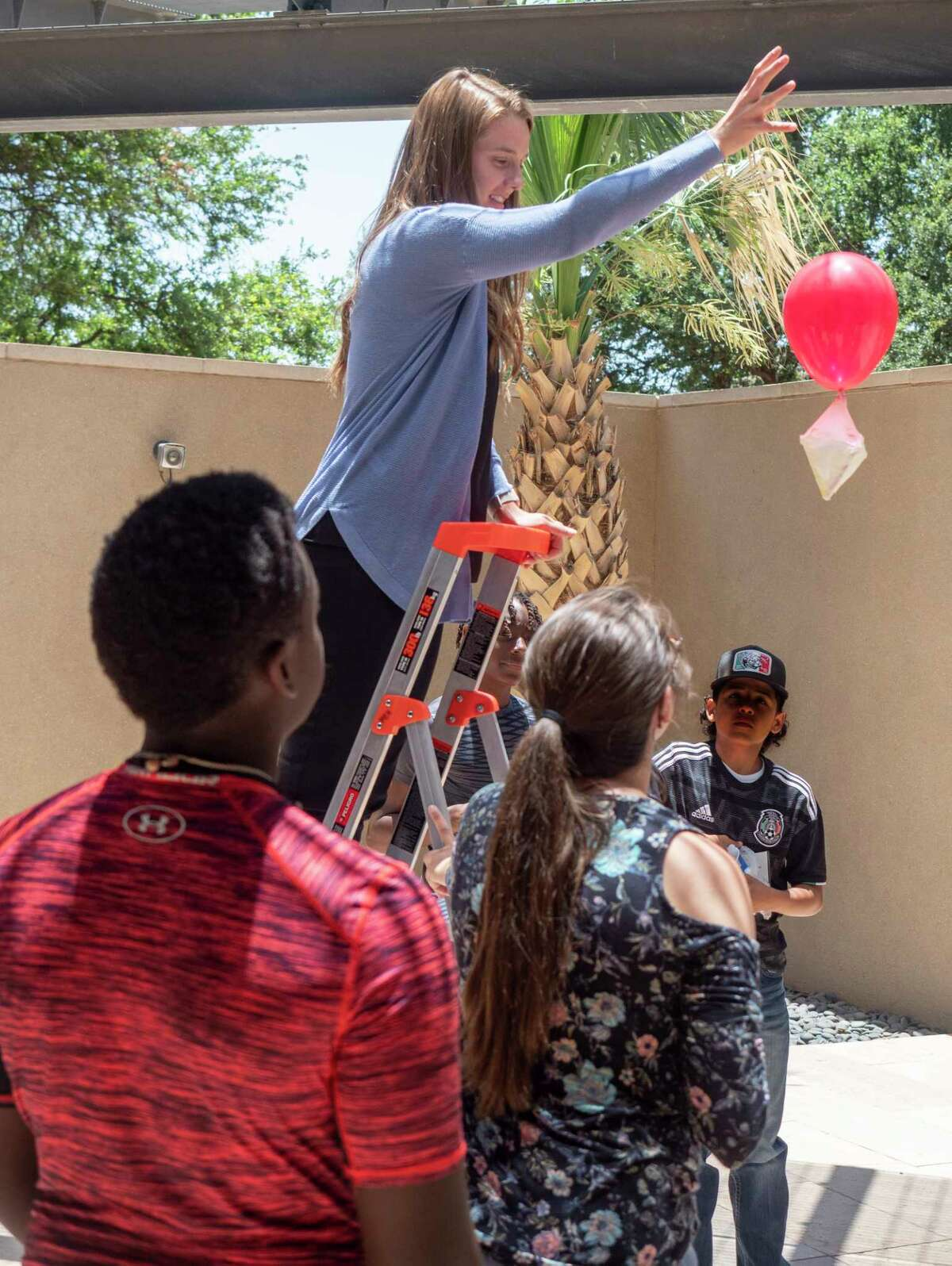 Diamondback Energy employee Kiley Hayes drops an encased egg to test different materials as she and others work with seventh and eighth graders from Opportunity Tribe 06/23/2021 during STEM Camp at Diamondback Energy. Tim Fischer/Reporter-Telegram