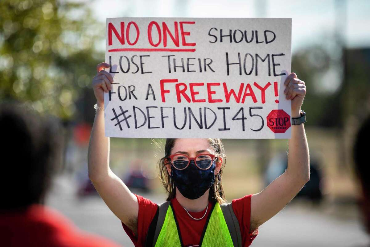 Organizer Chloe Cook holds a sign during a protest walk of the Interstate 45 expansion in Fifth Ward on Dec. 6, 2020.
