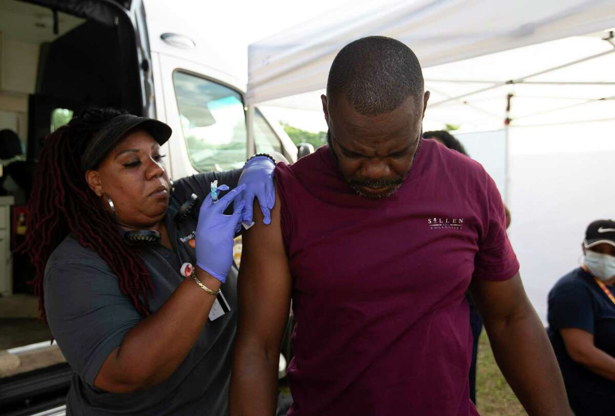 Houston Health Department Licensed Vocational Nurses Lisa Merchant administers a COVID-19 vaccine to John Gipson at Camz Food Truck & Entertainment Park Saturday, June 12, 2021, at Acres Homes in Houston. Gipson signed up to receive a shot after Houston Mayor Sylvester Turner came to the food truck park to urge people to be vaccinated.