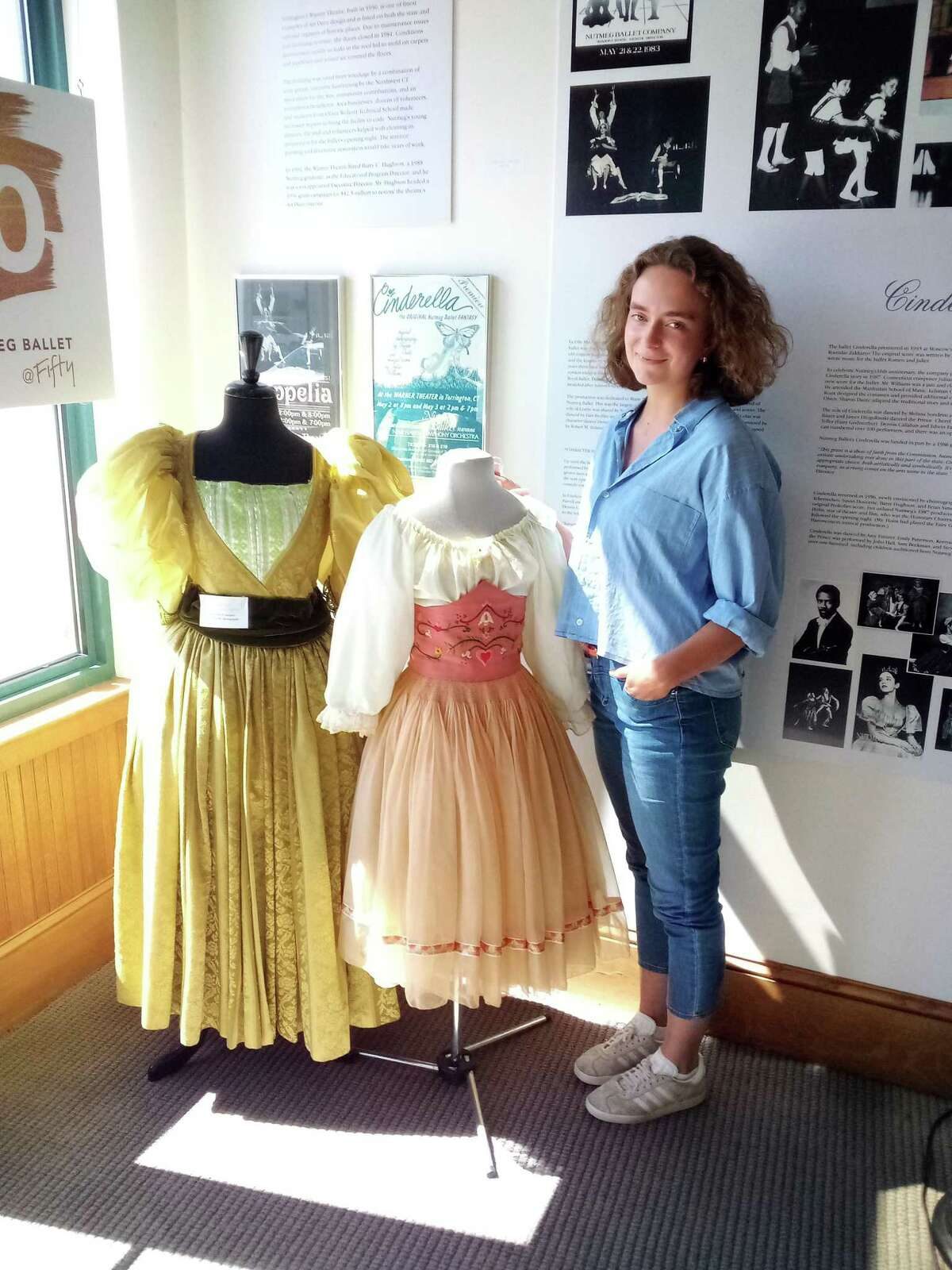 """Alma Evertz stands by a """"Coppelia"""" costume at the Nutmeg Conservatory, which was worn by her mother, artistic director Victoria Mazzarelli. Evertz is running the Torrington School of Ballet's summer program this year."""
